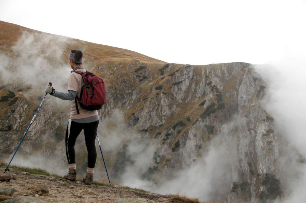 Hiker with trekking poles on edge of mountain