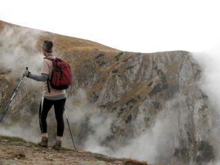 Hiker with trekking poles on edge of mountain