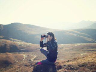 Girl spotting wildlife with binoculars